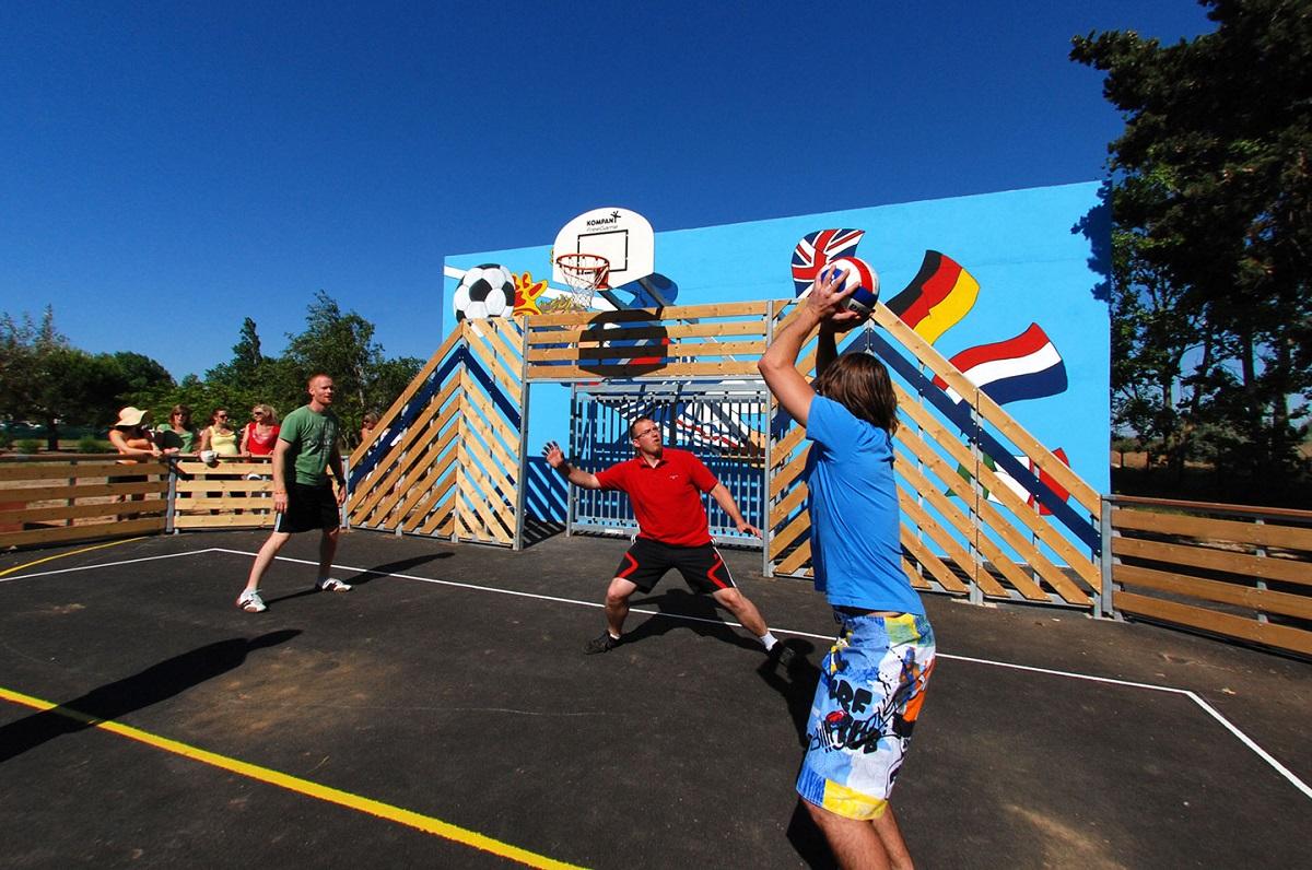 Des touristes jouent au basket.