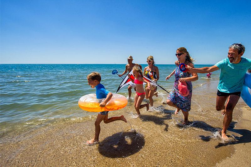 Famille courant sur la plage du camping à Vias-Plage