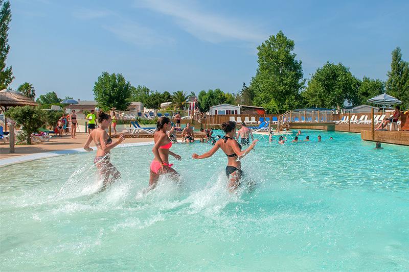 Jeunes courant dans la piscine du camping à Vias Plage