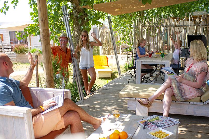 Voisins se saluant sur la terrasse d'un mobil-home premium au camping à Vias Plage.